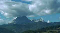 Densely clouds go over the mountain time lapse Stock Footage