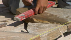 Stonemason draws line on stone before cutting CU Stock Footage