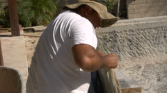 Stonemason draws line on stone before cutting Stock Footage