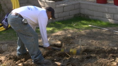 Man digs hole with Pickaxe  Stock Footage