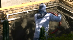 Construction worker applying Gunite Shotcrete to spa overhead  - stock footage