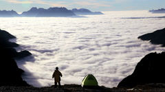 Hiker in the clouds on top of the Peaks in the Italian Dolomites, Italy Stock Footage