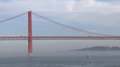 Bridge on fog river and sailboat in Lisbon Stock Footage