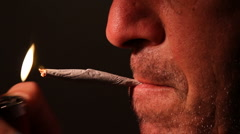 Man lights Marijuana joint inhales exhales Stock Footage