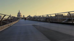 Male starting positions on millenium bridge London, UK and sprint over bridge Stock Footage