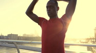 Stock Video Footage of Male stretching in red top, City of London, Olympic city in the background, UK