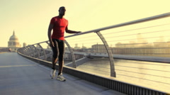 Male stretching in red top, City of London, Olympic city in the background, UK Stock Footage