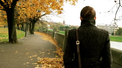 Young woman walking at autumnal park on yellow leaves, steadicam shot Stock Footage