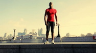Stock Video Footage of Male stretching in red top, City of London,