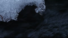 Stock Video Footage of Water is dripping from melting snow into a lively rivulet