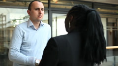 Business male and female in conversation in office corridor Stock Footage