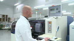 Operator at automated electronics assembly line Stock Footage
