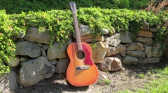 ACOUSTIC GUITAR SITS AGAINS Stock Footage