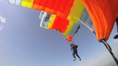 Parachutists flying under parachute in the clear blue sky Stock Footage