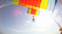 Parachutists flying under parachute in the clear blue sky above the sun Stock Footage