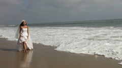 Handheld Shot of Bride Walking Along the Beach  Stock Footage