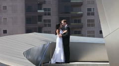 Wedded Couple Kissing Atop a Modern Building Stock Footage