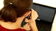 Woman talking on cellphone and working on laptop Stock Footage