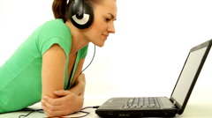 Woman with headphones in front of the laptop, isolated Stock Footage