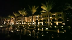 Fountains and palms in front of office Paris Gallery Group at night in Dubai, Stock Footage