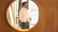 Stock Video Footage of Businesss male talking on headset in office view trough office door window