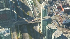 Aerial, traffic and train below, late afternoon shadows Stock Footage