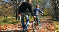 Stock Video Footage of father teaches his son to ride a bicycle