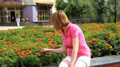 HD Young girl looking at marigold flowers Stock Footage