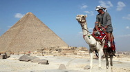 Egyptian Man on Camel in Front of Great Pyramid Stock Footage