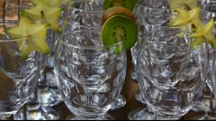 Hand pouring water to wine glasses with kiwi and carambola Stock Footage