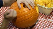 Stock Video Footage of Carving a pumpkin on table