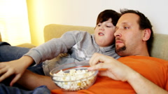 Father and son wathing tv and eating popcorn Stock Footage