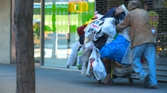 Homeless man sadly pushing grocery cart full of bags Stock Footage