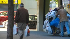 Homeless man pushing shopping cart, long shot Stock Footage