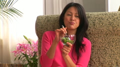 Young woman eating a salad Stock Footage