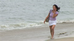 Young woman walking along shoreline at beach Stock Footage