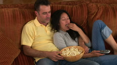Young couple on couch with popcorn watching TV Stock Footage
