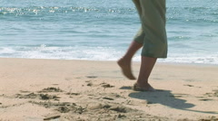 Young woman twirling at the beach with pier in background Stock Footage