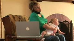 New mother with laptop and cell phone holding new baby Stock Footage