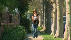 Mother walking outside holding baby in sling Stock Footage