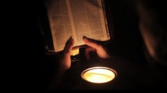 Reading by candle light Stock Footage
