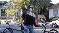 Young woman waits for event while made up with skeleton face paint - 3 - stock footage