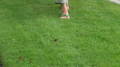 Female feet with flip flops walking through grass Stock Footage