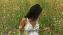 Young woman in meadow of flowers wearing white sun dress Stock Footage
