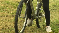 Young woman on bike in rural setting talking on cell phone Stock Footage