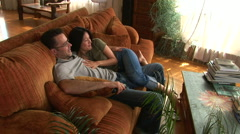 Young couple on couch using remote to watch TV - stock footage