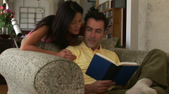 Romantic young couple reading a book and kissing Stock Footage