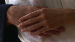 Portrait of young couple in bathrobes kissing and hands touching Stock Footage