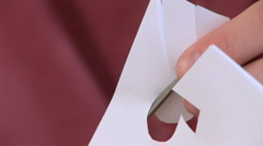 Close up of male hands cutting out paper dolls Stock Footage