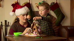 Mother and toddler son with gingerbread house at Christmas Stock Footage